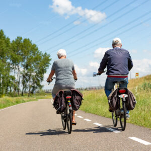 Older couple biking on asphalt road in the dutch village of Leiderdorp. Bike with hearing impaired sign.