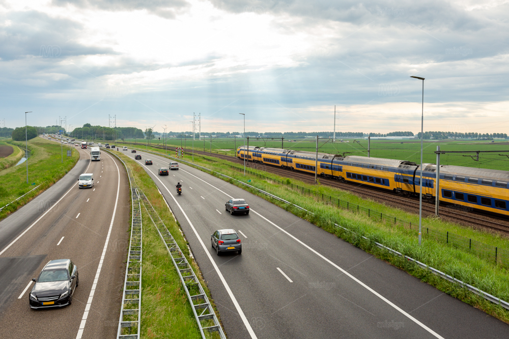 Cars on the A44 highway and a train near the village of Abbenes in the Netherlands.
