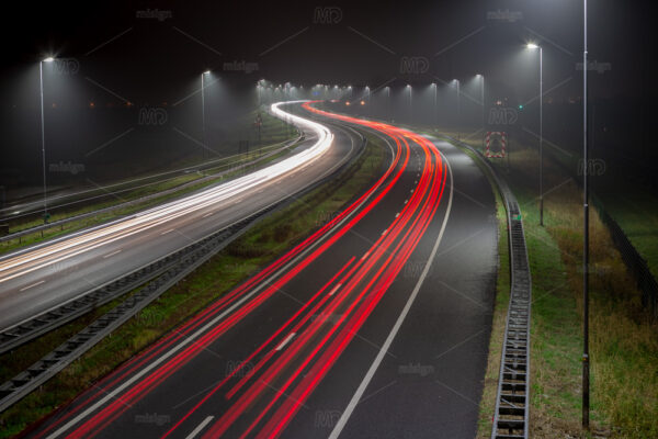 White headlights and red tail lights on a foggy evening on the A44 highway near the village of Abbenes in the Netherlands.