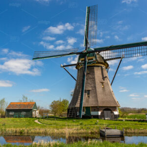 A historic windmill with reflection on the water in the green fields and a blue cloudy sky of Rijpwetering in The Netherlands.
