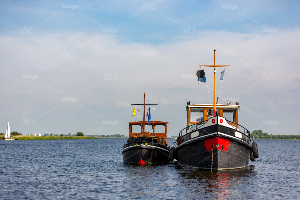 2 old tugboats at anchor on lake 't Joppe in the Netherlands.