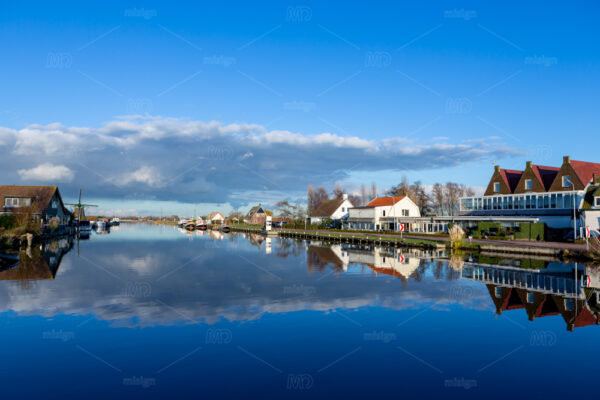 Reflections of clouds in the Ringvaart canal at the Lisserdijk in Lisse. On a sunny day in the Netherlands.