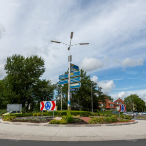 Cars entering a roundabout with traffic direction signs on the van Pallandtlaan in the village of Sassenheim in the Netherlands.