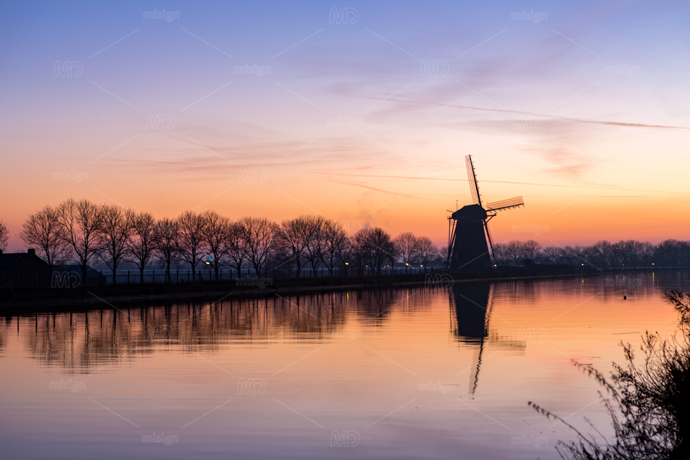 "Sundown at the historical windmill ""the Googermolen"" with reflection in the Ringvaart canal in Nieuwe Wetering the Netherlands."