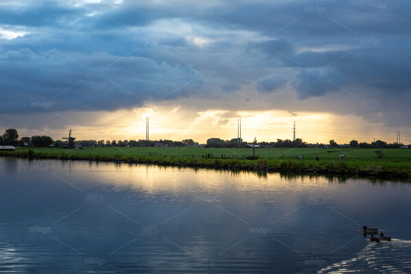 Bright sunrays shine on the high poles of the electricity grid through the village of Nieuwe Wetering. On a eary morning over the Ringvaart canal in the Netherlands.