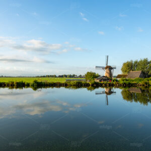 "Windmill ""the Adermolen"" in the morning with a clear reflection in the water of the Ringvaart canal in Abbenes, the Netherlands."