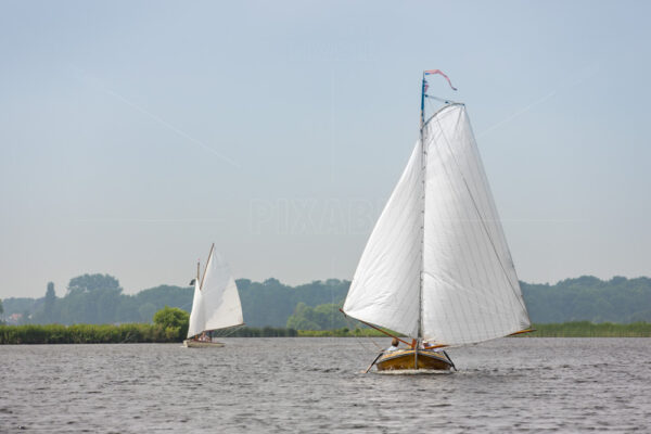 A historic sailboat with 2 people sailing on the lake 't Joppe in the village of Warmond in the Netherlands.