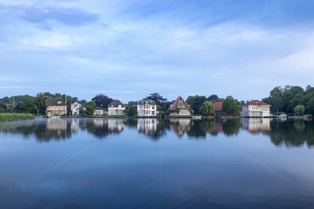 A row of beautiful villas on the Warmonderleede with a view of the island of Koudenhoorn in the South-Holland village of Warmond in the Netherlands