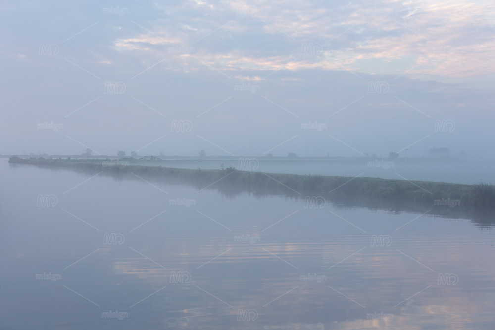 A foggy morning water landscape of the Norremeer of the South-Holland Kagerplassen in the Netherlands.