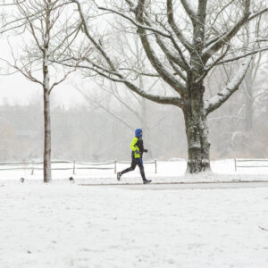 A man running in the Amsterdam Vondelpark on a snowy winter day in december in the Netherlands.