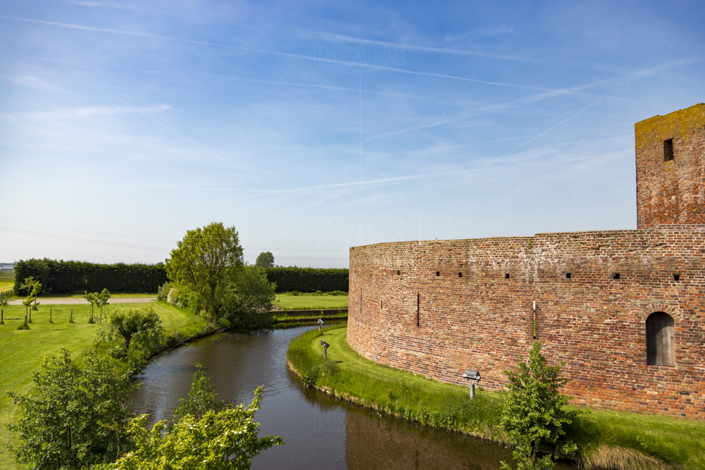 The moat and garden around the ruin castle Teylingen in the South-Holland village of Sassenheim in the Netherlands. On a blue and cloudy day.