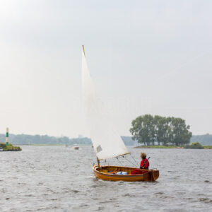 A sailboat with a woman sailing on the Kaag in the village of Sassenheim in the Netherlands.