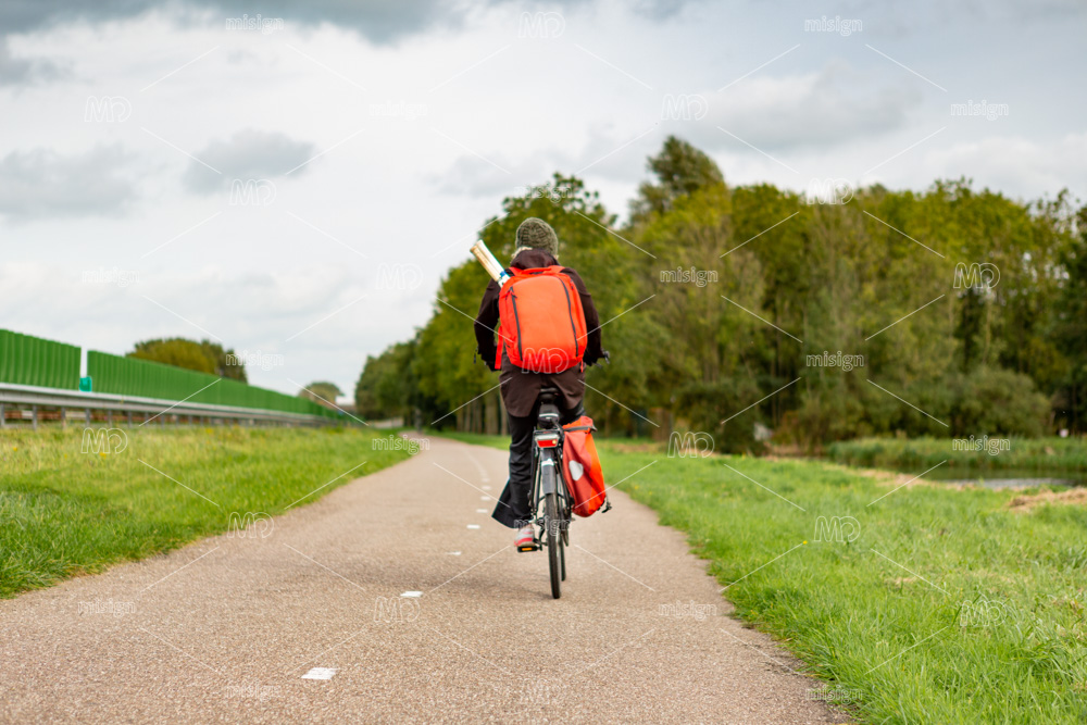 A lonely biker with a backpack near the A44 highway in the south-Holland village of Sassenheim in the Netherlands. © Pixable photostock 2020