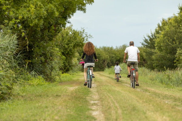 Young family on a country bike ride in the beach village of Caorle in the Provice of Veneto in Italy.