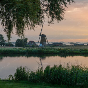 Sunrise and fogg over the meadows of the Zwanburgerpolder at the Kagerplassen with the Zwanburgermill in the South-Holland village of Warmond in the Netherlands.