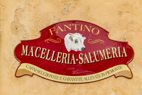 """Old style sign with the words """"Butcher's shop delicatessen"""" and """"Selected and guaranteed meats raised in Piedmont"""" on a light brown plastered wall. In the Pimonte village Busca of in Italy."""