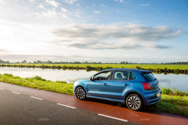 A blue parked car on the side of the road near the ringvaart canal in the North-Holland village of Abbenes on a cloudy day in the Netherlands.