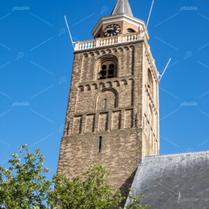 The roman tower of the Protestant church an the gray slated roof located in the centre of the South-Holland village of Rijnsburg in the Netherlands. On a clear blue and sunny day.