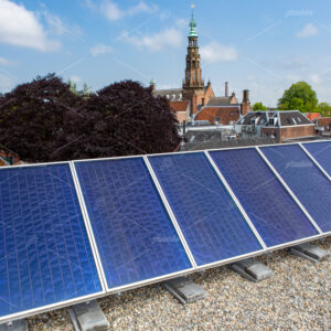 Solar panels on the roof in the South-Holland city of Leiden in the Netherlands. On the background the town hall of Leiden.