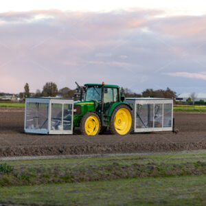 A modern tractor on farmland with a custom-built bulb planting machine with cabin in the South-Holland town of Voorhout in the Netherlands.