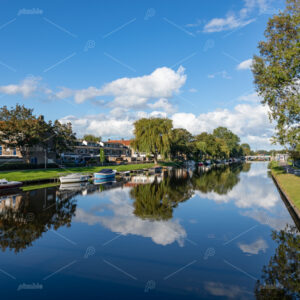 Boats moored on the side of the Oegstgeester canal in the South-Holland village of Rijnsburg in the Netherlands. On a cloudy and sunny day.