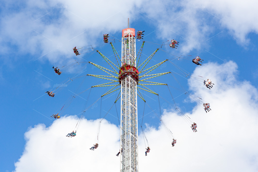 People in a fairground carousel swinging high up in the air against a cloudy blu sky. On the 3th of oktober in the south-Holland city of Leiden in the Netherlands.