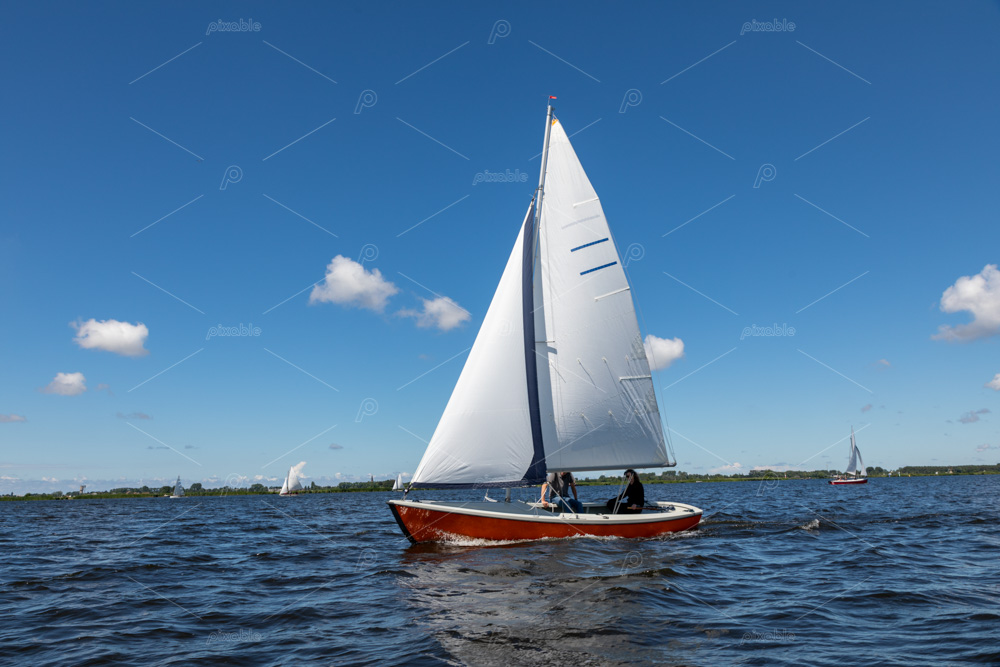 A red sailing boat on the Kagerplassen with 2 people sailing in the South-Holland municipality of Warmond in the Netherlands. On a beautiful day with a blue sky.