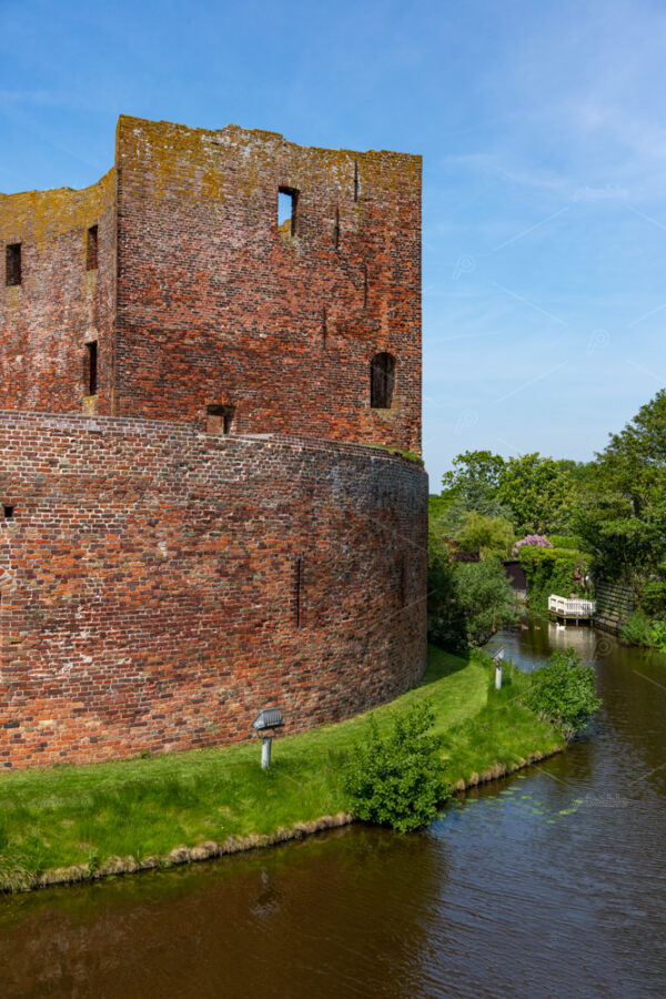 Southside with the moat of the ruin castle Teylingen in the south-holland village of Sassenheim in the Netherlands.