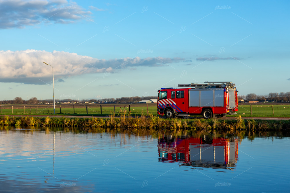 A red firetruck driving on the Lisserdijk along the river the Ringvaart in the village of Lisse in the Province of North-Holland in the Netherlands