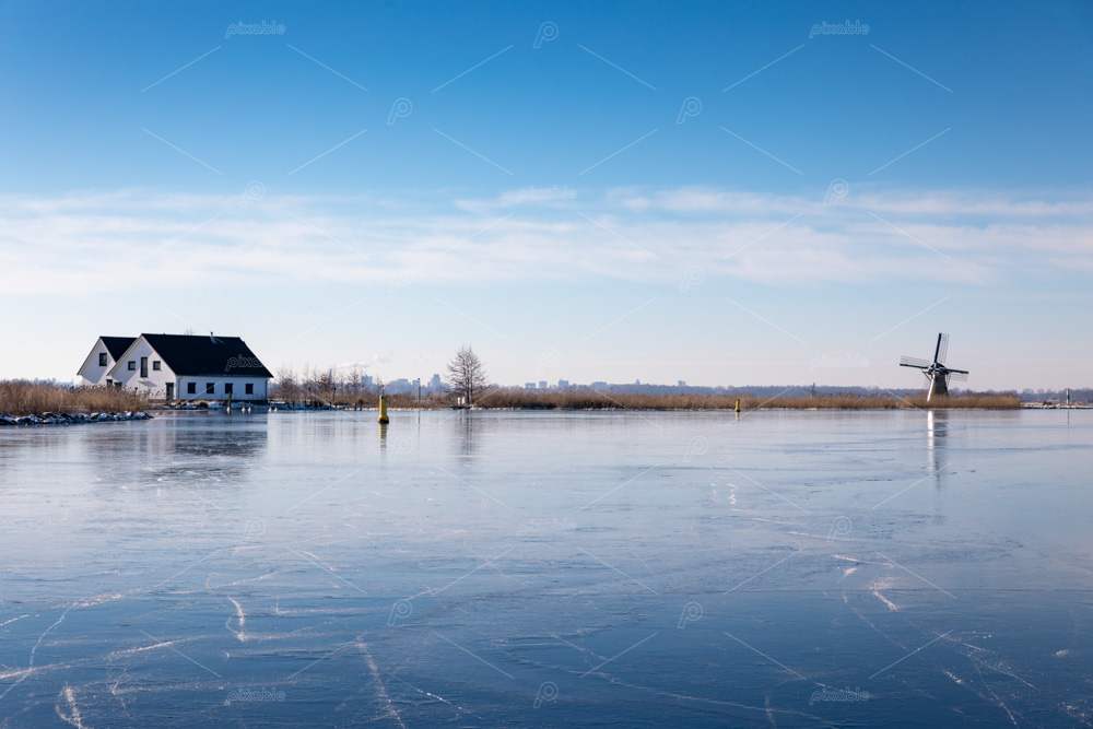 ice on the Dieperpoel (Kagerplassen) in front of a windmill (de Kok) and house on the Kogjespolder in Teylingen
