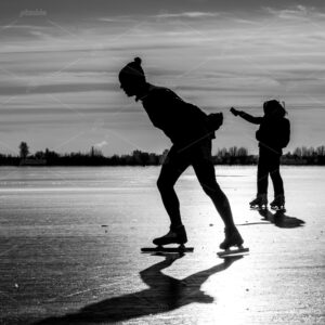Man skating in a winter landscape with shiny ice, across the frozen plains of the Kagerplassen in the south-holland municipality of Warmond in the Netherlands.