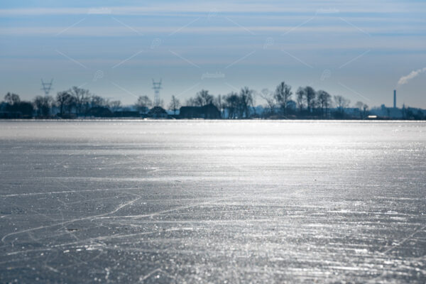 A winter landscape with shiny ice, across the frozen plains of the Kagerplassen in the south-holland municipality of Warmond in the Netherlands.