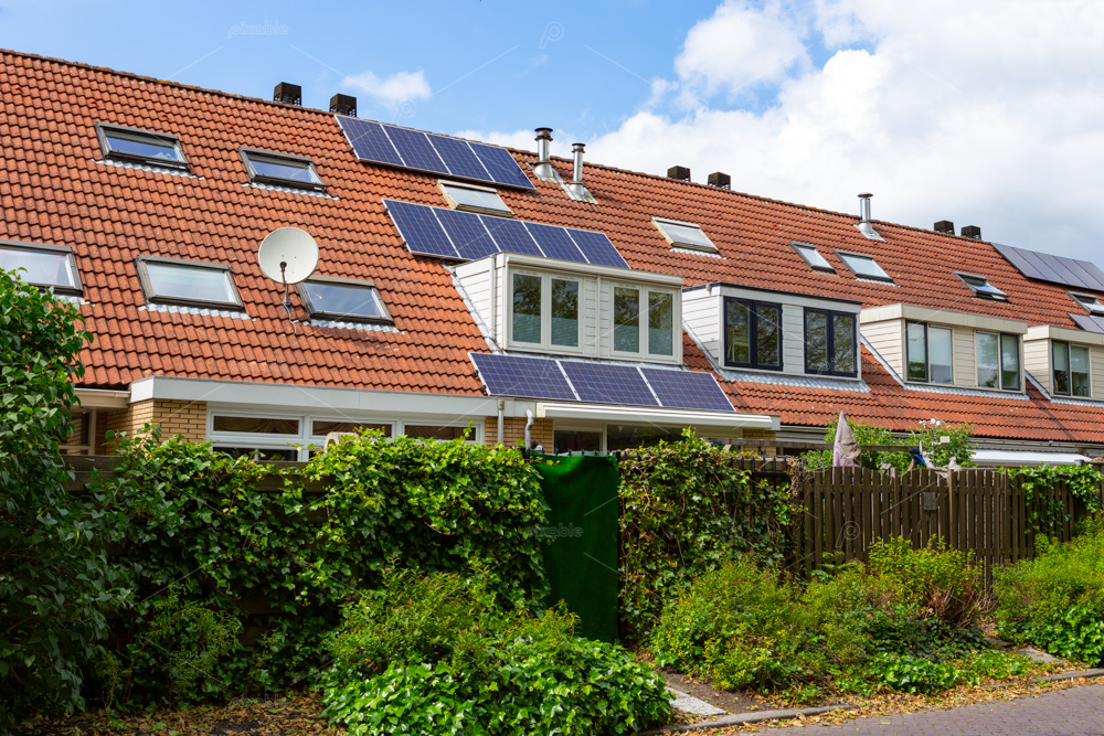 Solar panels on the orange tiled roof of a terraced house with a dormer in the South-Holland village of Sassenheim in the Netherlands.
