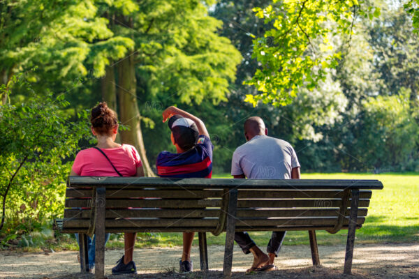 Three people sitting on a bench in a sunny and green Amsterdam Vondelpark in the Netherlands.