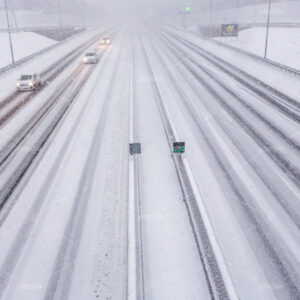 Cars in a heavy snow storm on the A10 highway in Amsterdam on a winter day in december in the Netherlands.